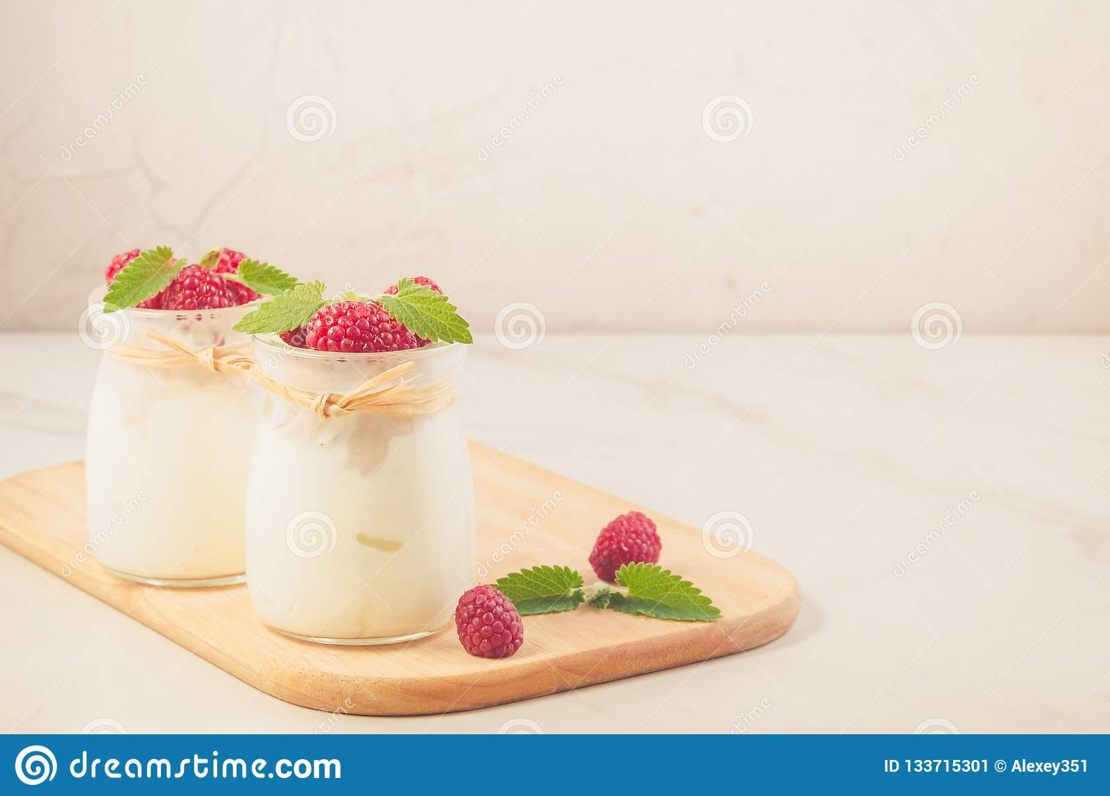 two banks with yogurt with raspberry and mint/two banks with yogurt with raspberry and mint on a wooden tray, copy space