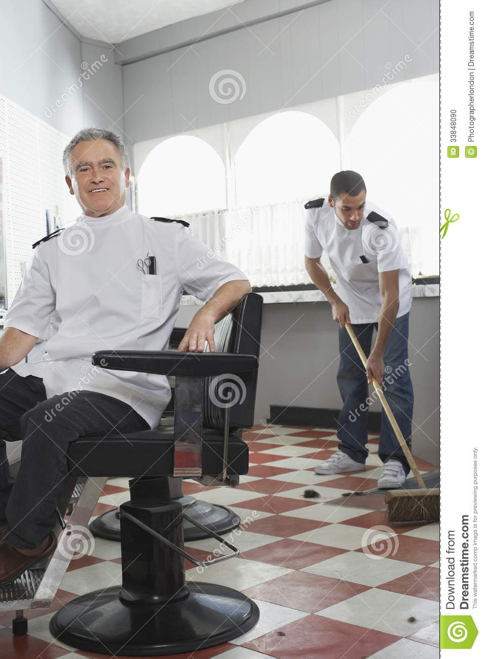Portrait of happy senior male barber with apprentice sweeping floor at ...