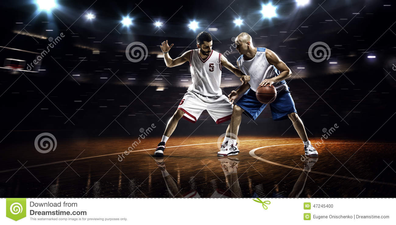 Two basketball players in action in gym in lights.