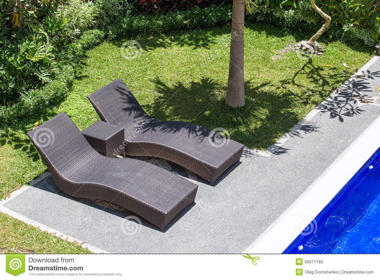 Two Beach Chairs Next To A Swimming Pool In A Tropical Garden Stock Image
