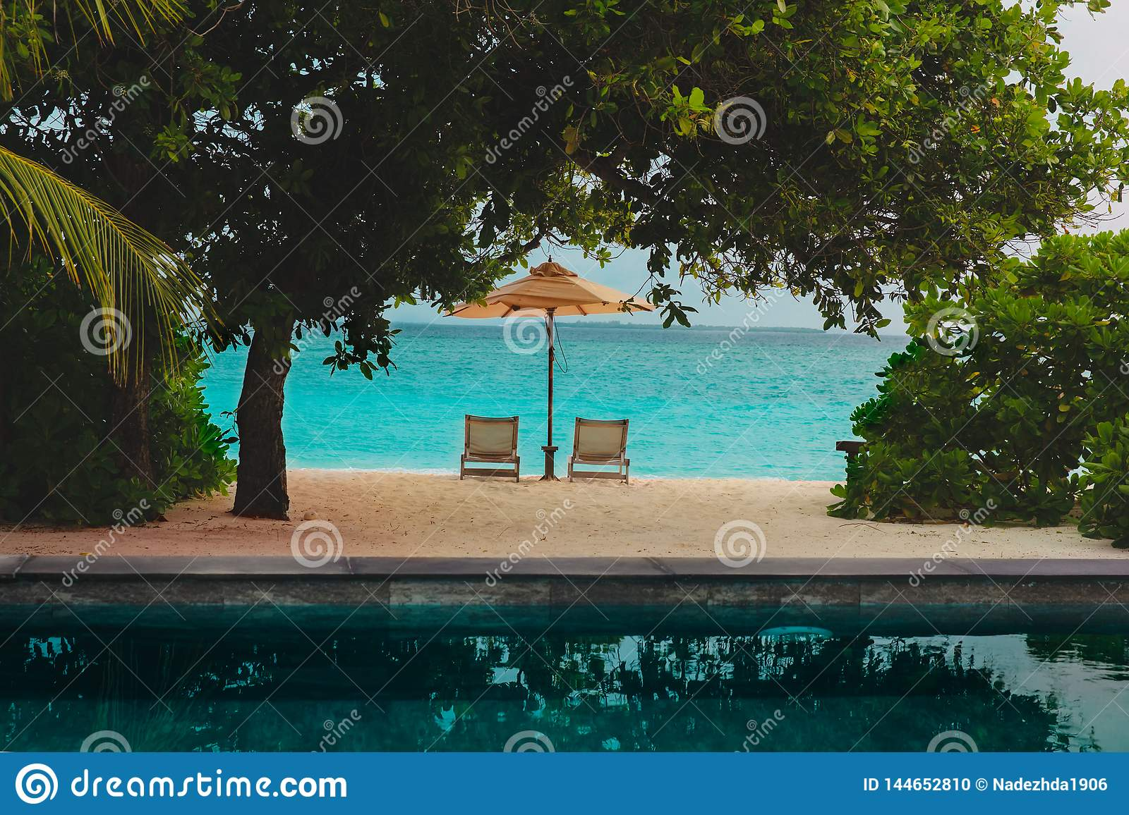 Two beach chairs on tropical resort, vacation concept