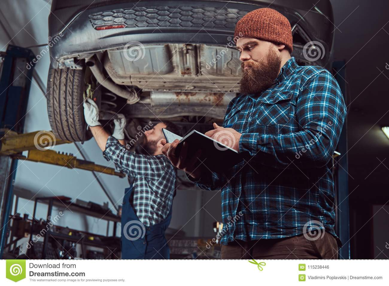 two bearded brutal mechanics repair a car on a lift in the garage
