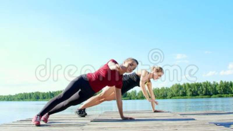 Two beautiful, athletic blonde women, doing coordination and balance  exercises synchronously  Lake, river, blue sky and