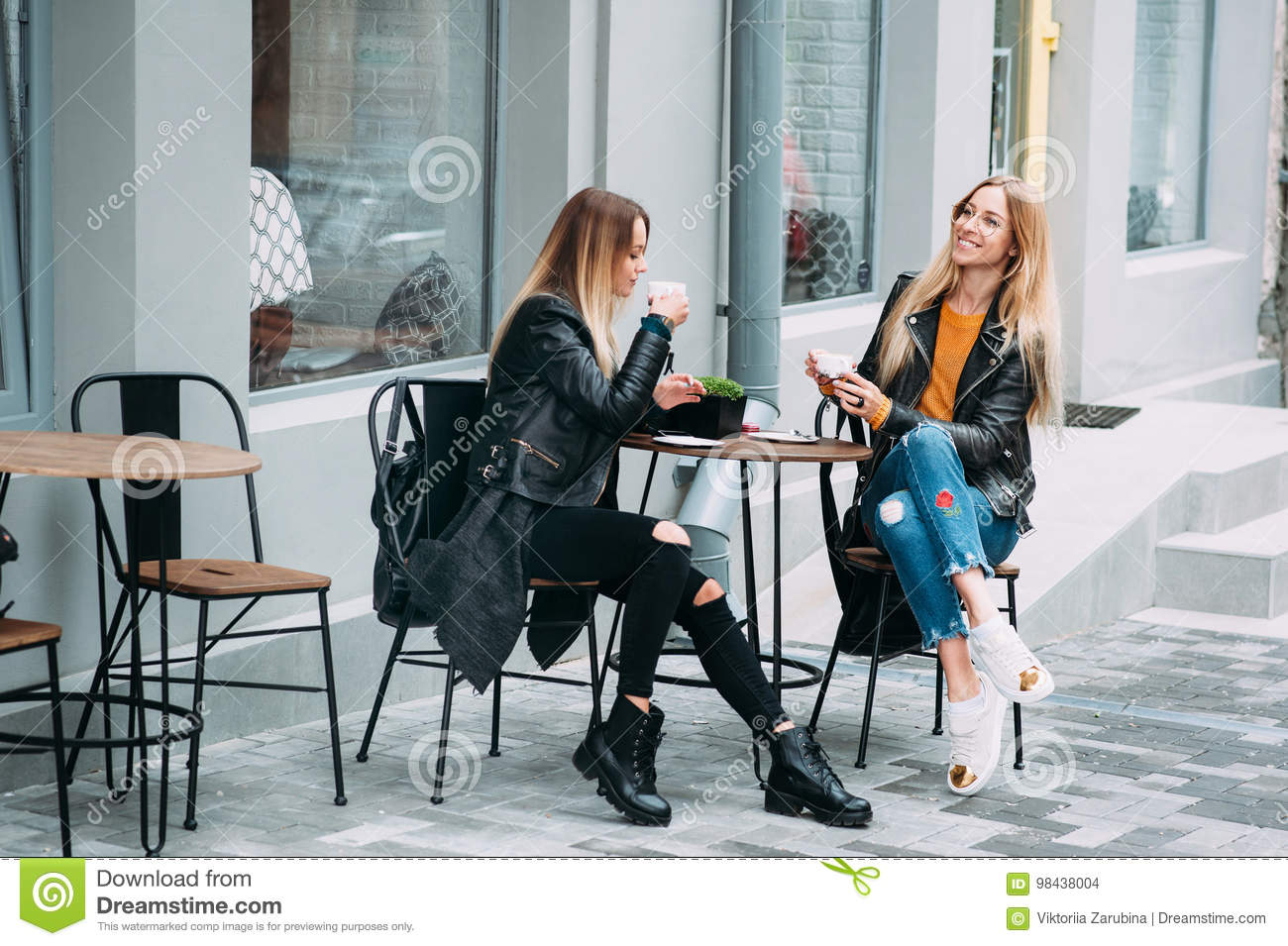 Two beautiful attractive stylish women are sitting outdoor in cafe drinking coffe and tea talking and enjoying great day.