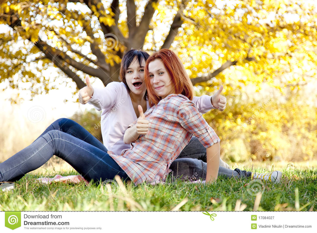 Two beautiful girlfriends at the autumn park
