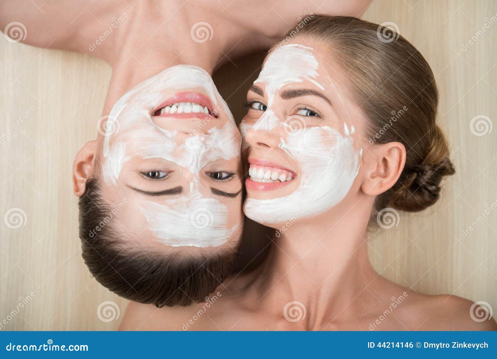 two beautiful girls applying cream mask and stock photo