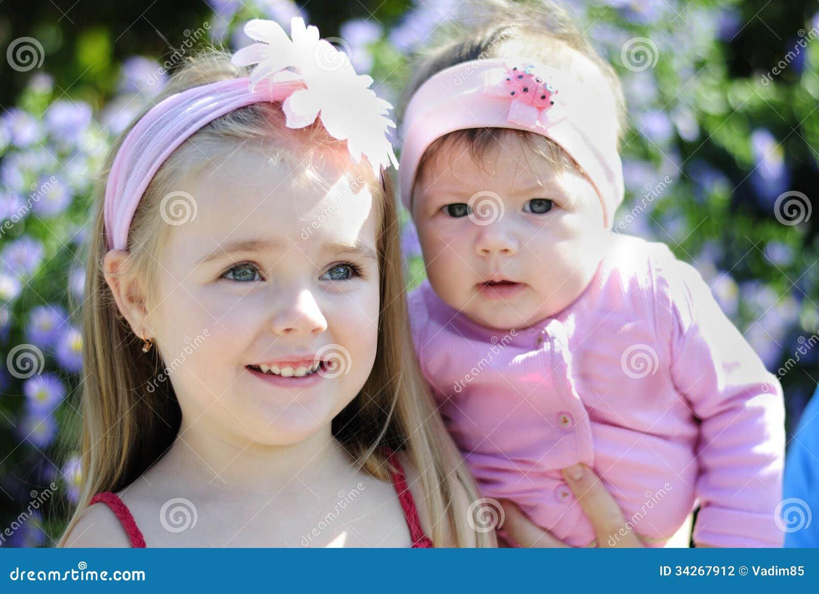Two beautiful girls near a flower stock photo image of children two beautiful girls near a flower izmirmasajfo
