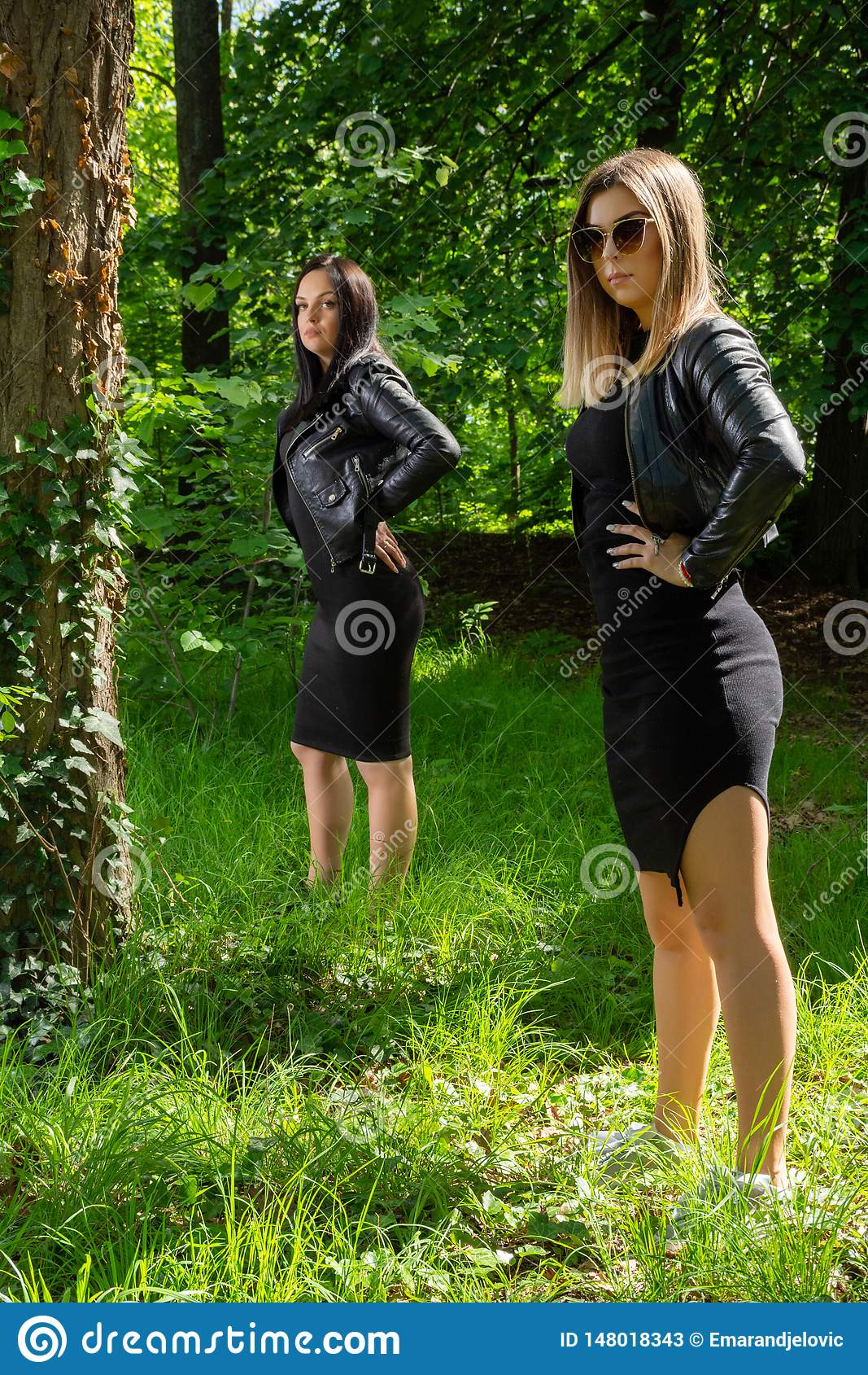 Two beautiful girls posing in a forest on a sunny spring day