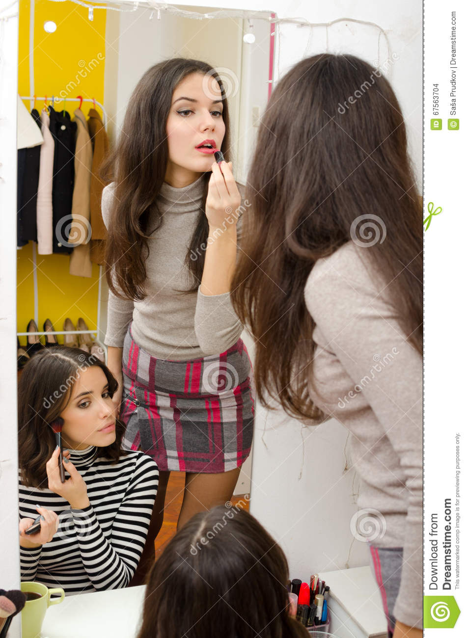 Two Beautiful Girls Putting Makeup In Front Of Mirror At Home Stock