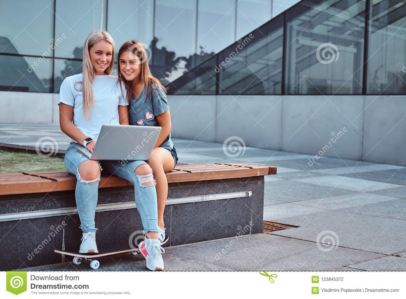 Two beautiful girls sitting holds a laptop and looking at a camera while sitting on the bench on background of the
