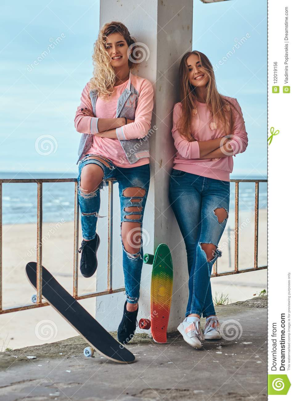 Two beautiful girls in trendy clothes posing with skateboards near a guardrail against a sea coast.