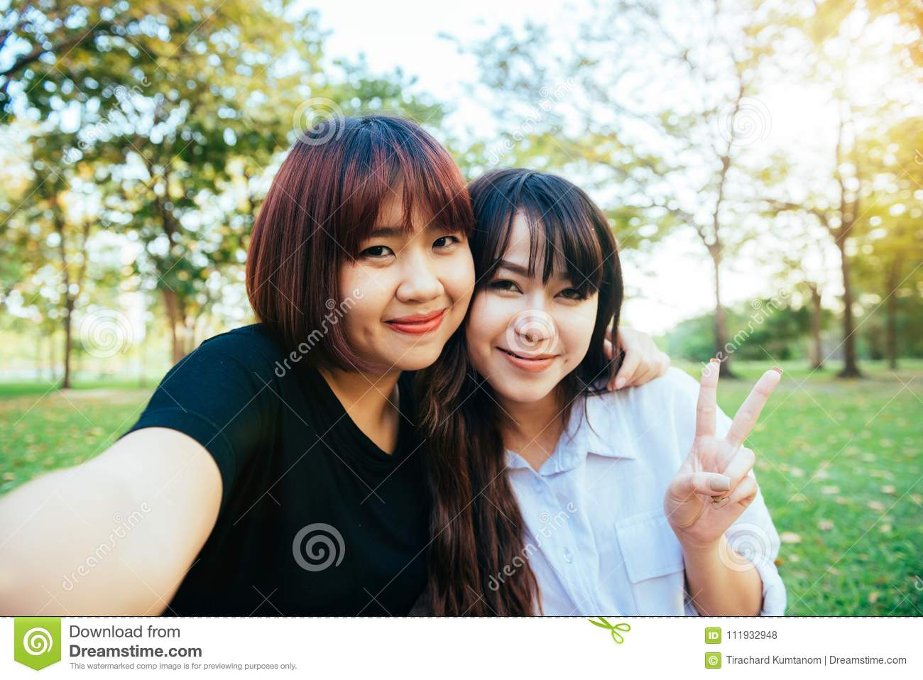 4e565a76f48 Two beautiful happy young asian women friends having fun together at park  and taking a selfie.