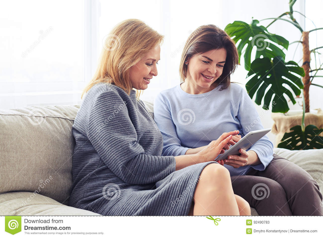 Two beautiful madams surfing on Internet in laptop