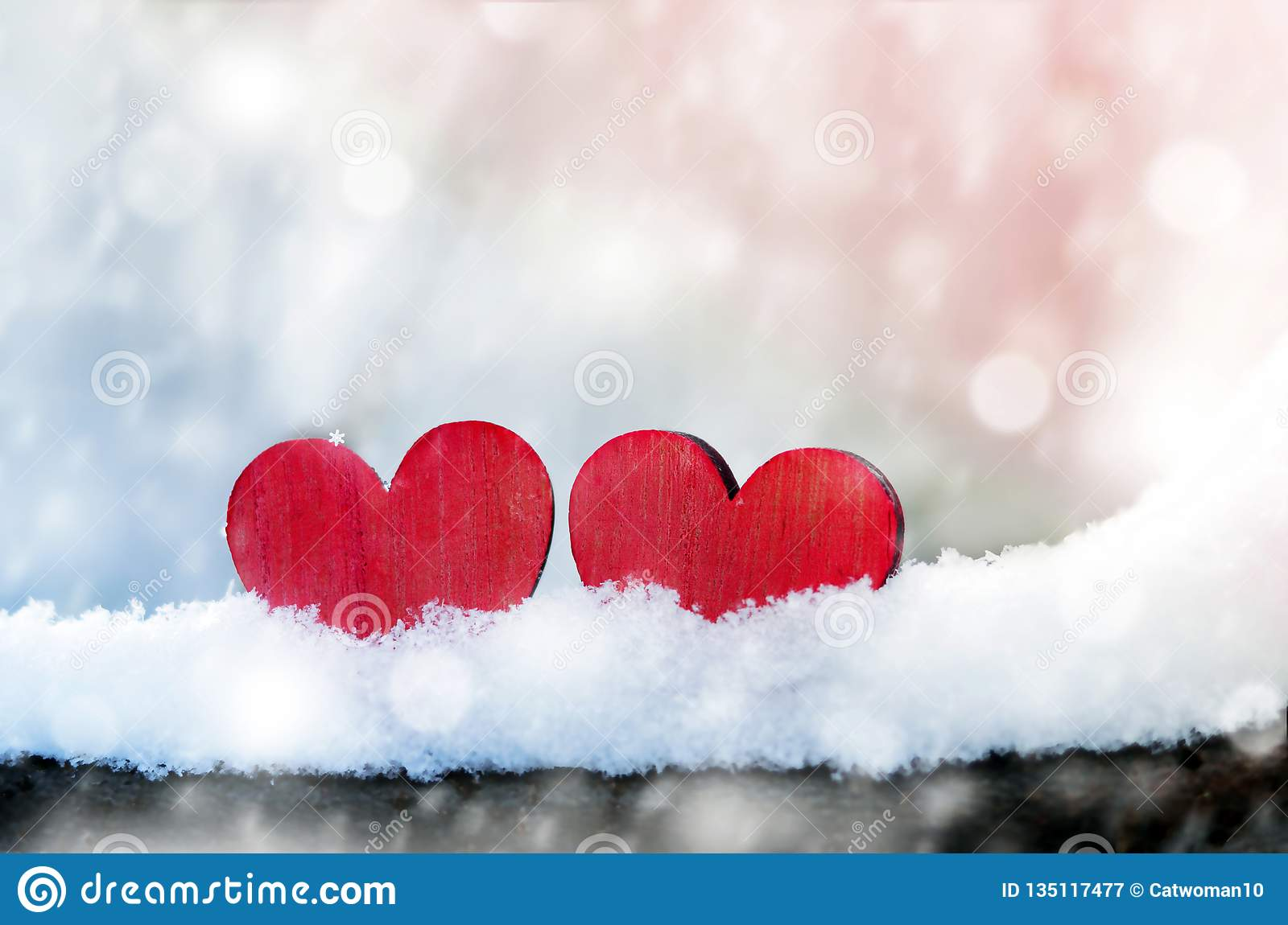 Two beautiful romantic vintage red hearts together on a white snow winter background. Love and St. Valentines Day concept