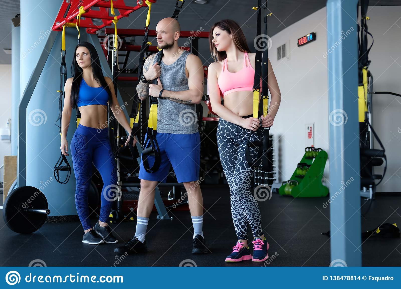 Two beautiful sportive girls with their coach holding functional loops while standing in the gym