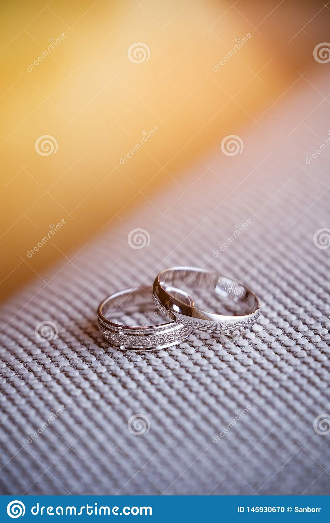 Two beautiful white gold engagement rings with diamond stones lie on the fabric with a rough texture. Wedding ring