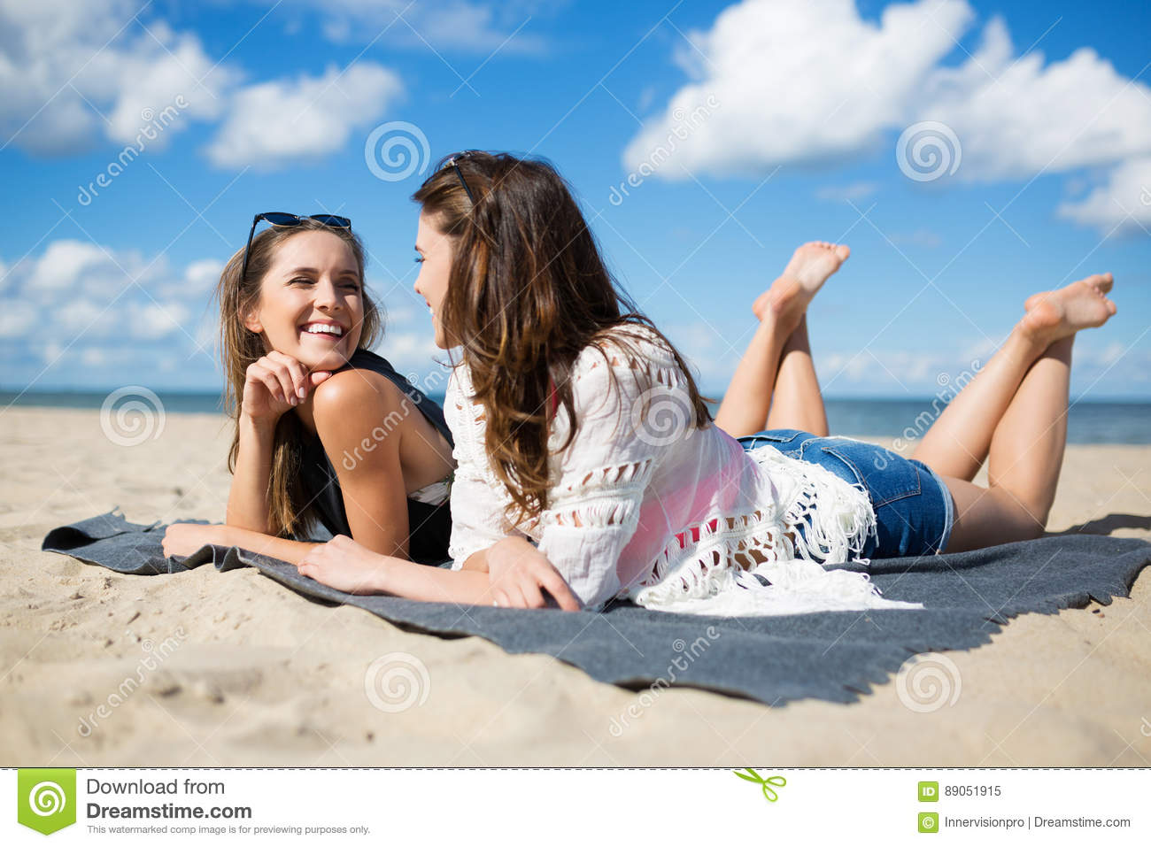 Two beautiful women lying on beach talking and laughing