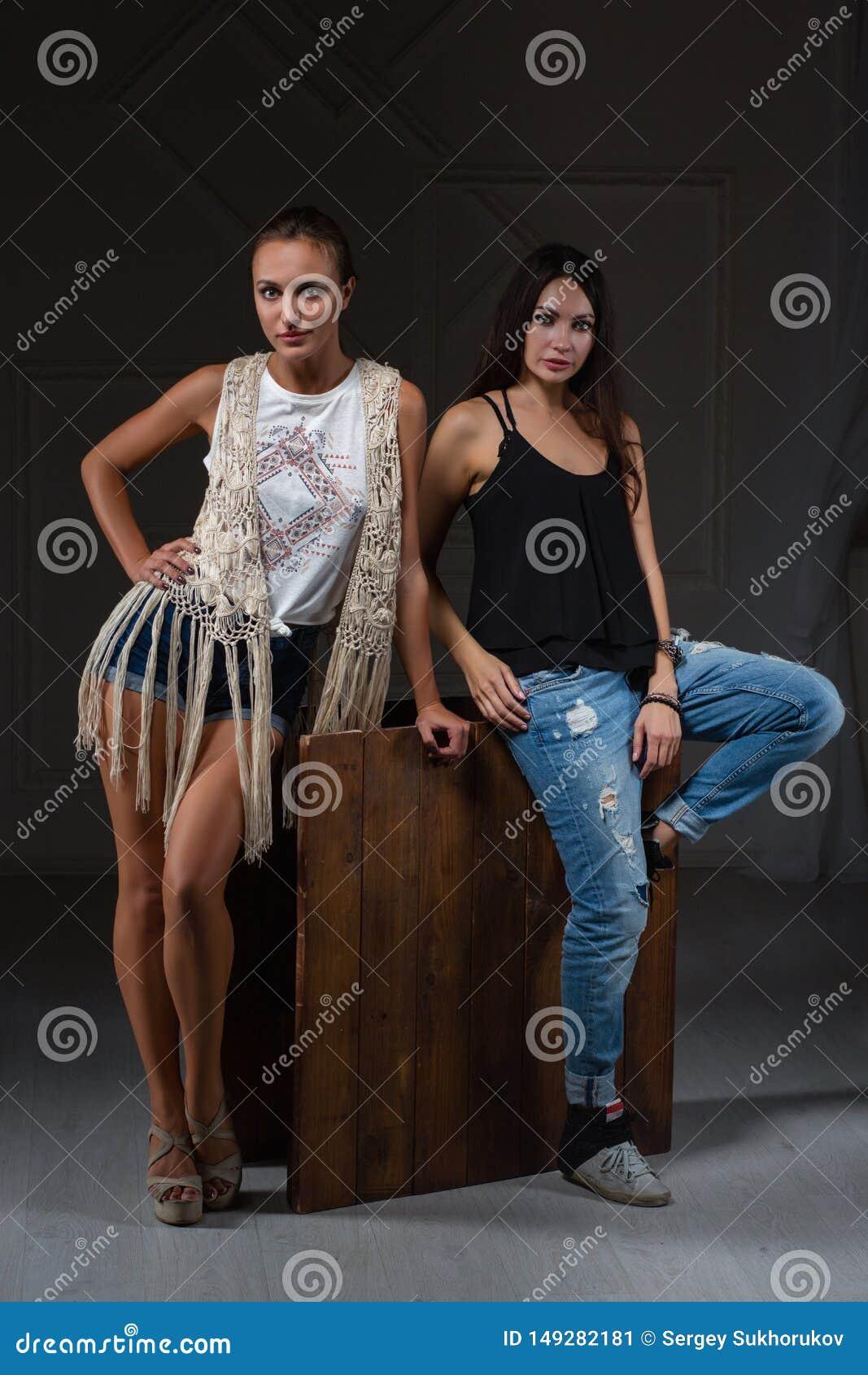 Two beautiful women posing in a studio