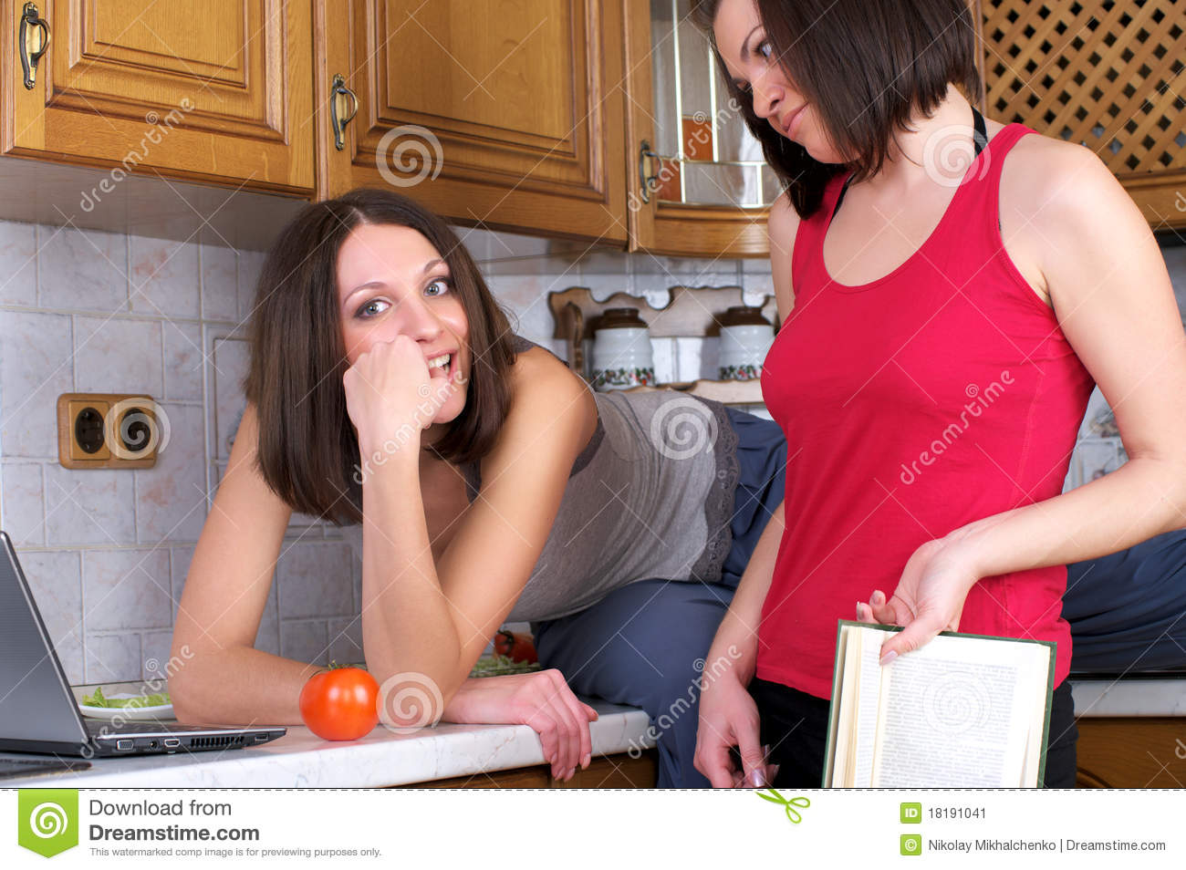 Two beautiful women trying to cook