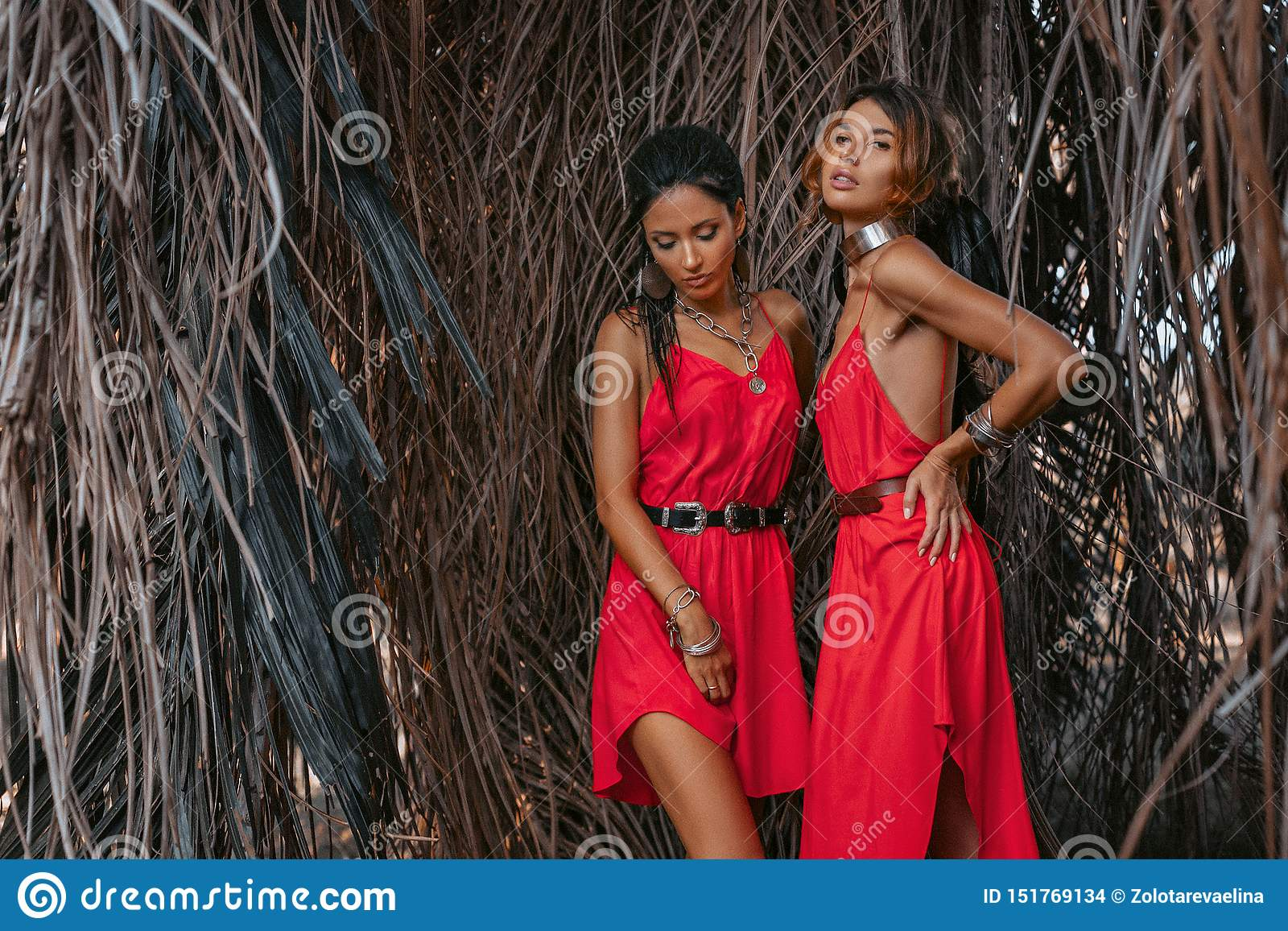 Two beautiful young fashionable models in red dresses outdoors at sunset