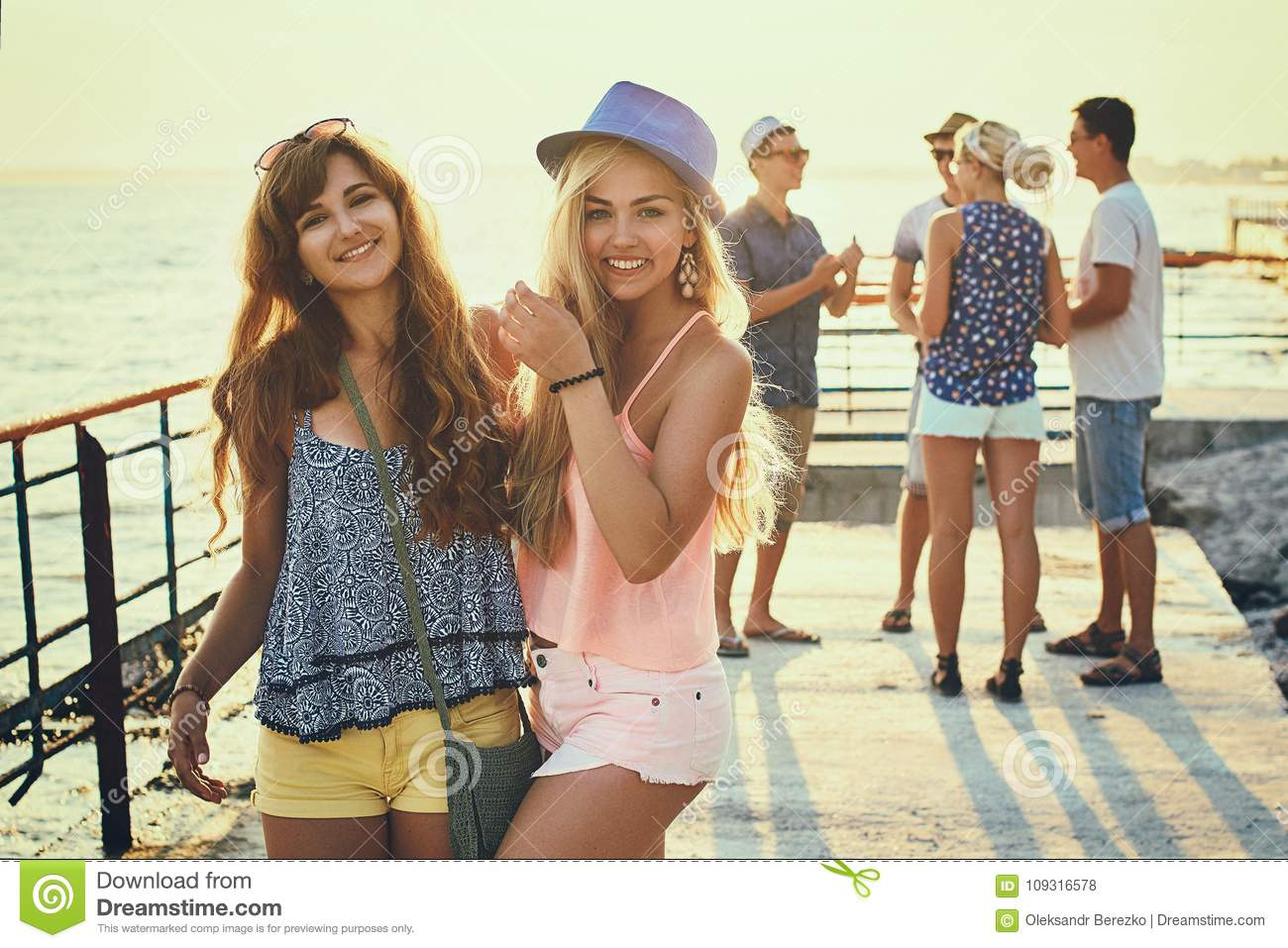 Two beautiful young girls having fun at the evening seaside with group of their friends on background toned in vintage