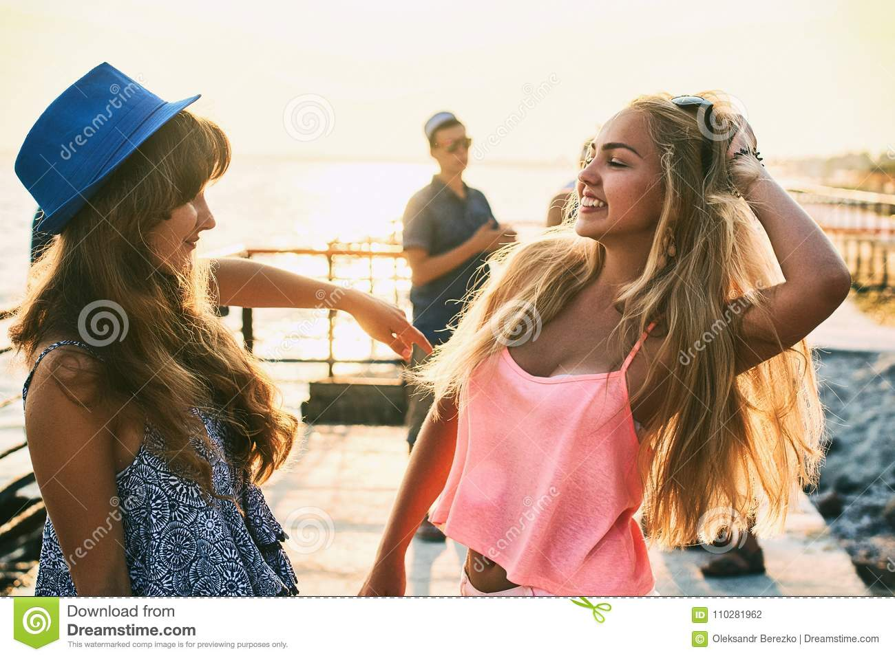 Two beautiful young girls having fun at the evening seaside with group of their friends on background