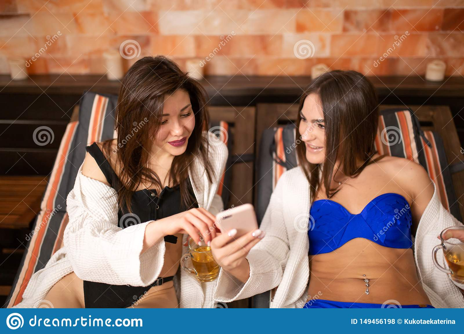Two beautiful young girls in swimsuits lay on wooden lounger in the sauna are discussing the news while looking into the phone