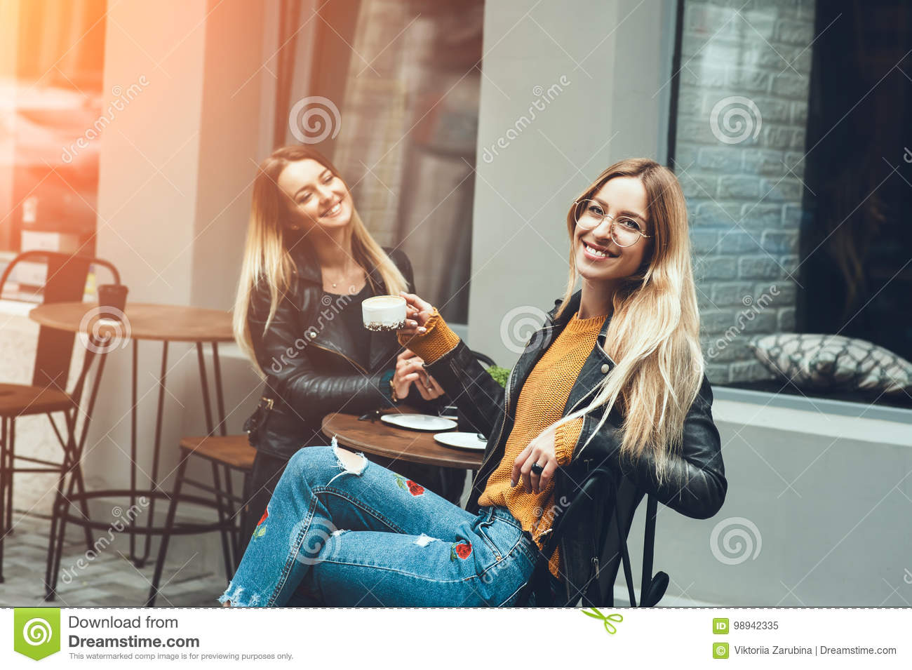 Two beautiful young women in fashion clothes having rest talking and drinking coffee in restaurant outdoor.
