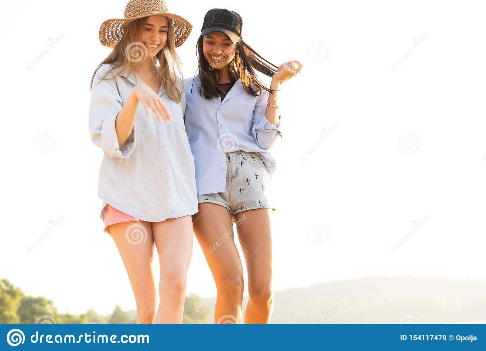 Two beautiful young women strolling on a beach. Female friends walking on the beach and laughing on a summer day.