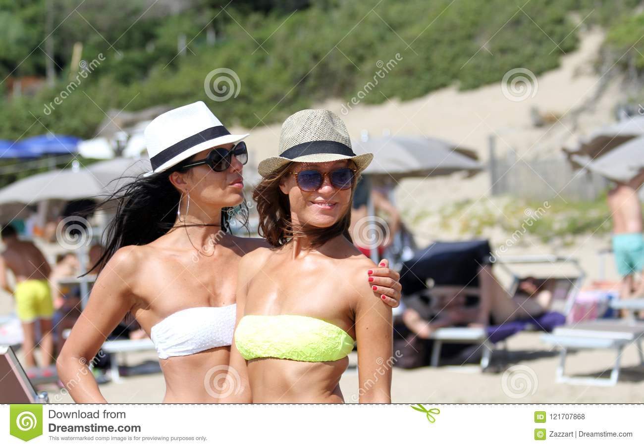 Two beautiful young women strolling on a beach. Female friends walking on the beach and laughing on a summer day, enjoying summer
