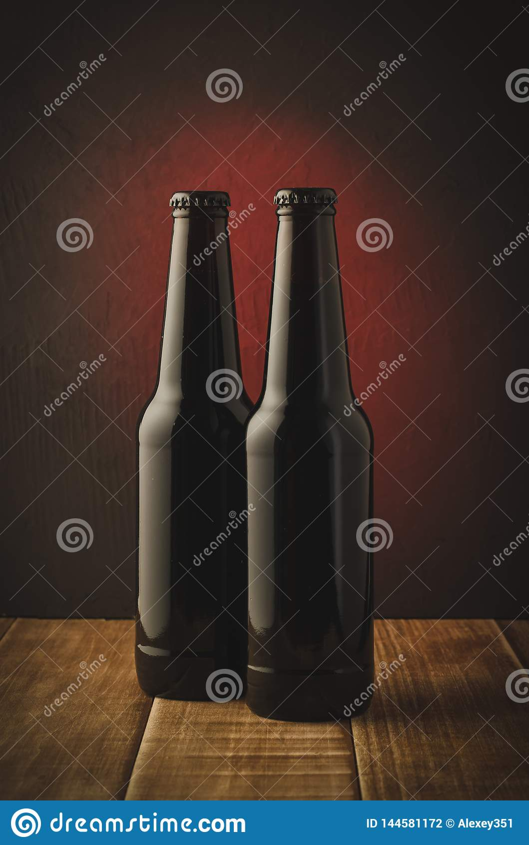 two beer bottles a dark background with red light/two beer bottles a dark background with red light. Selective focus
