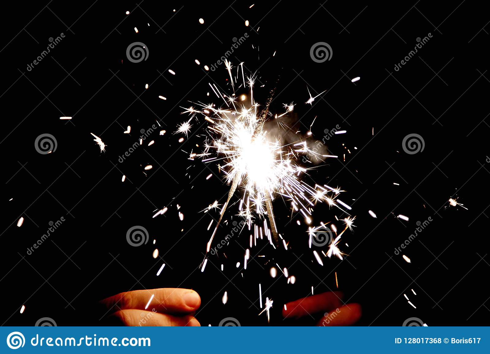 Two Bengal fire in hands sparkles on black background