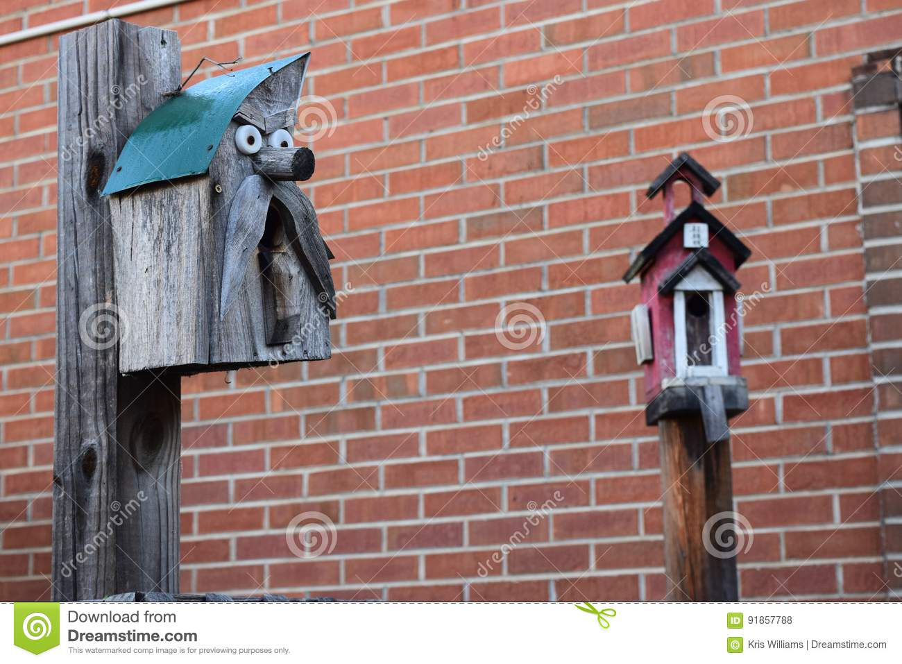 Two birdhouses with a brick wall background