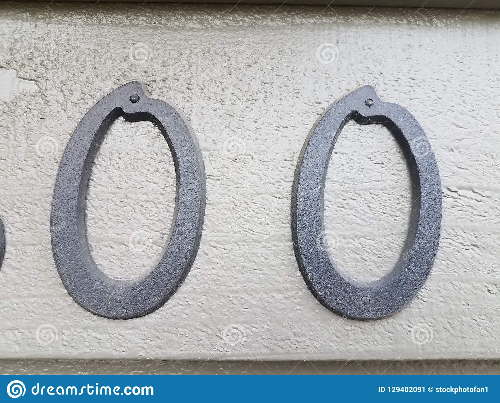 Two black number zero on grey paint. Wall stock image