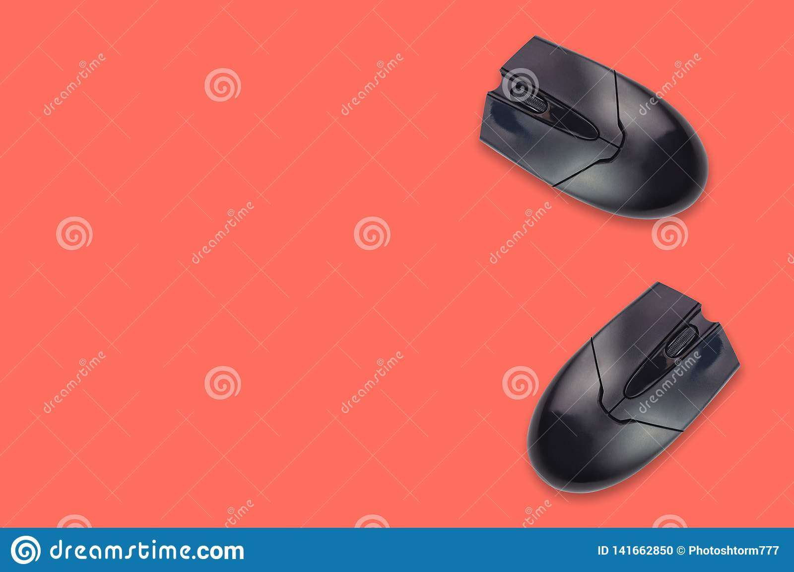Two black plastic optical computer mouses on office table coral color. Top view. Copy space for your text