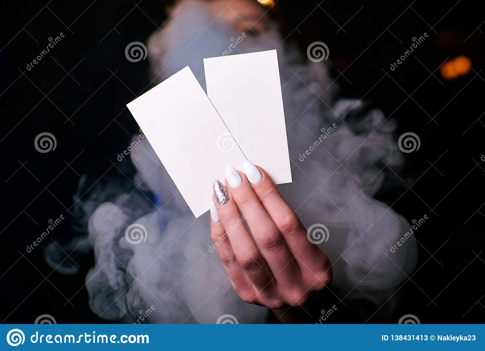 two blank white business cards in a woman`s hand
