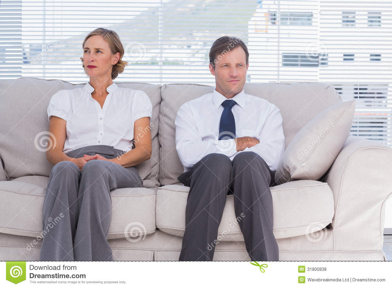 Two Bored Business People Sitting On Couch Stock Photo ...