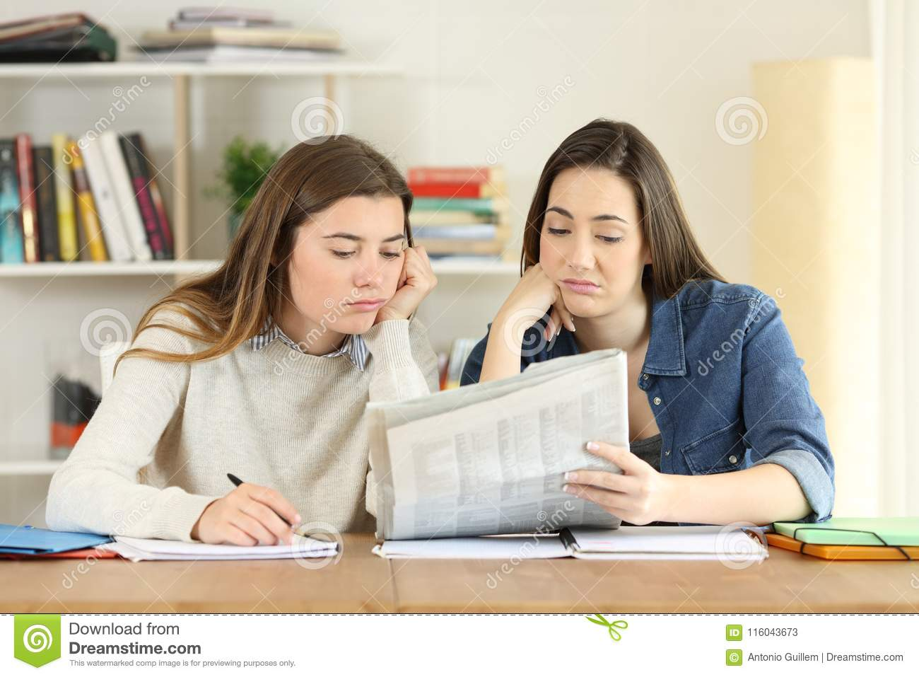 two bored students reading a newspaper stock image - image of home