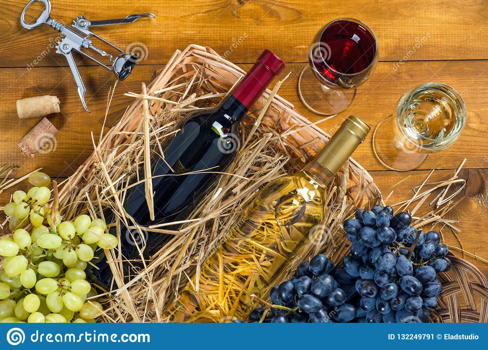 1ba4b8e0c309a3 Two bottles and glasses with wine in a basket with hay