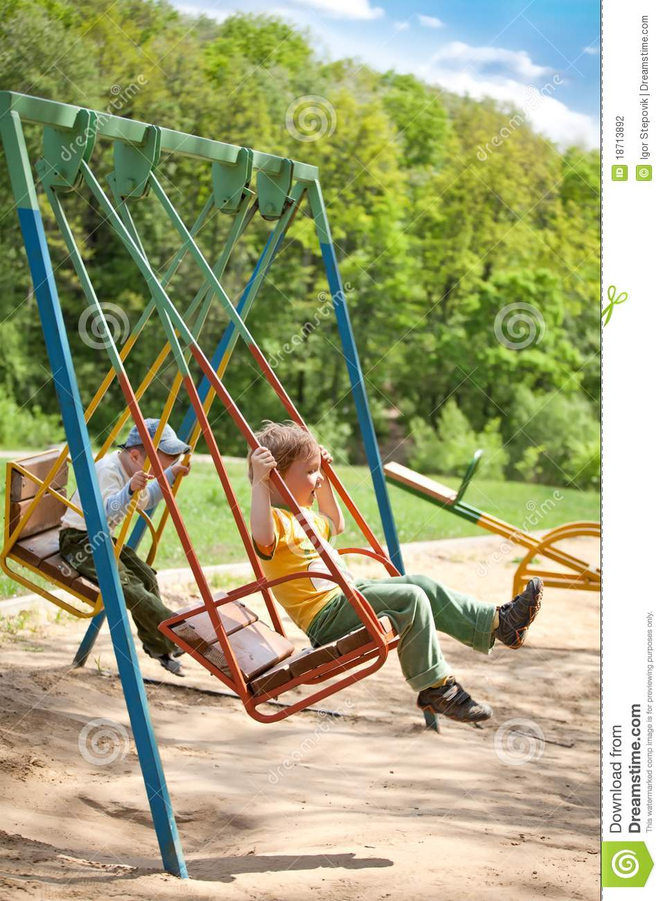 Two Boy Swinging On A Swing In The Park Stock Photo