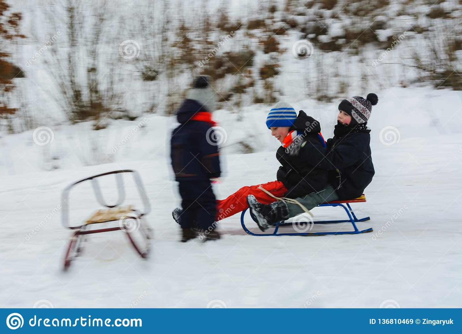 The two boys descend on sledges, and the girl waits for them, their movement is visible