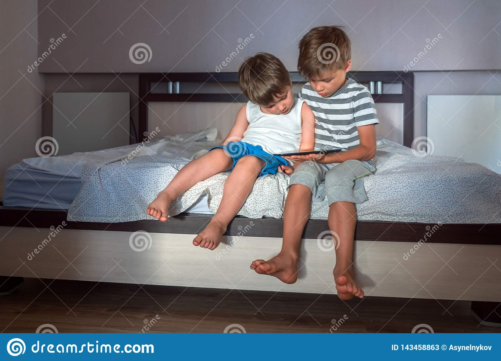 Children and gadgets. Two boys with tablet on the knees. Home schooling concept. Preschooling background. Home