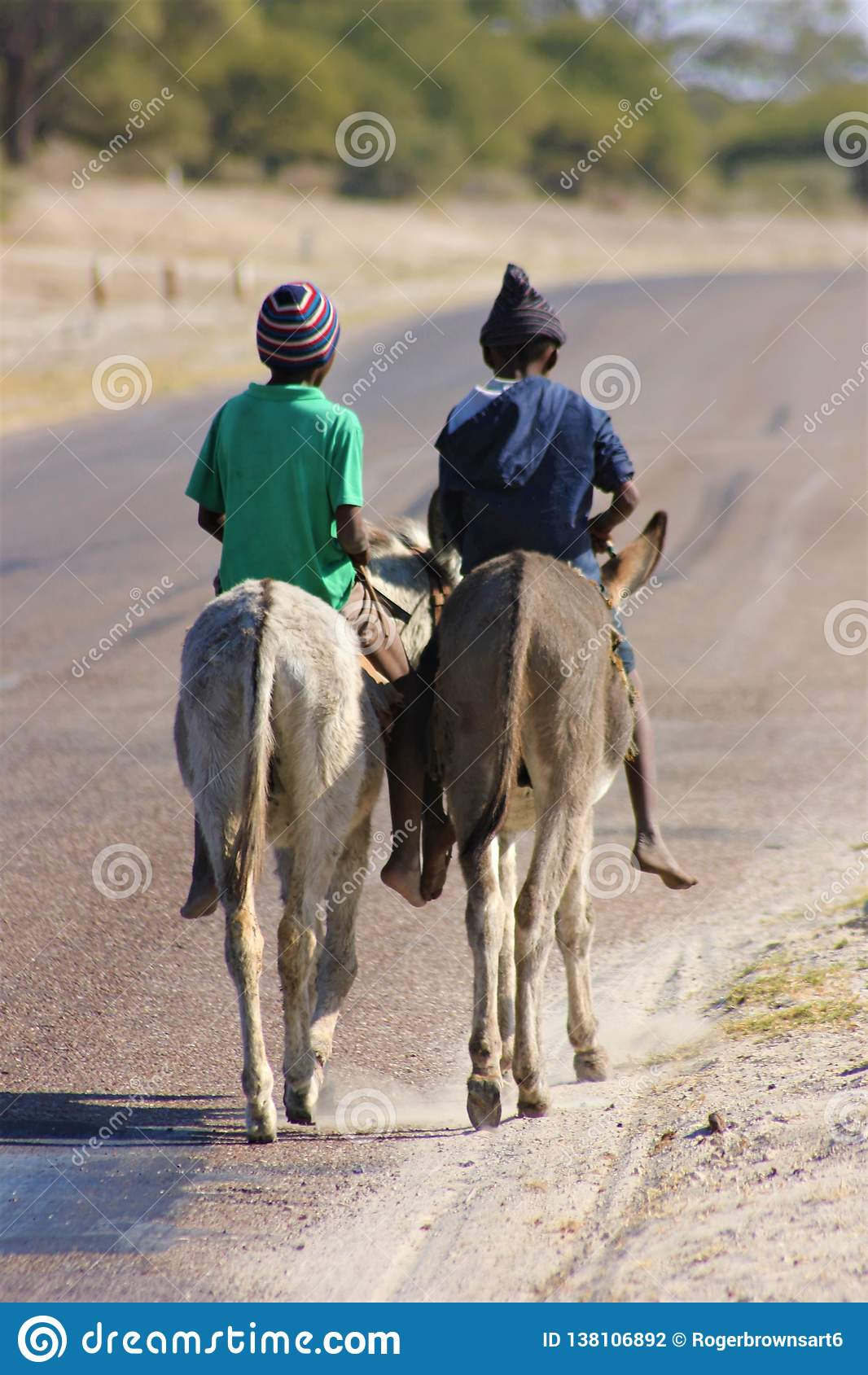 Two boys riding donkeys in Africa