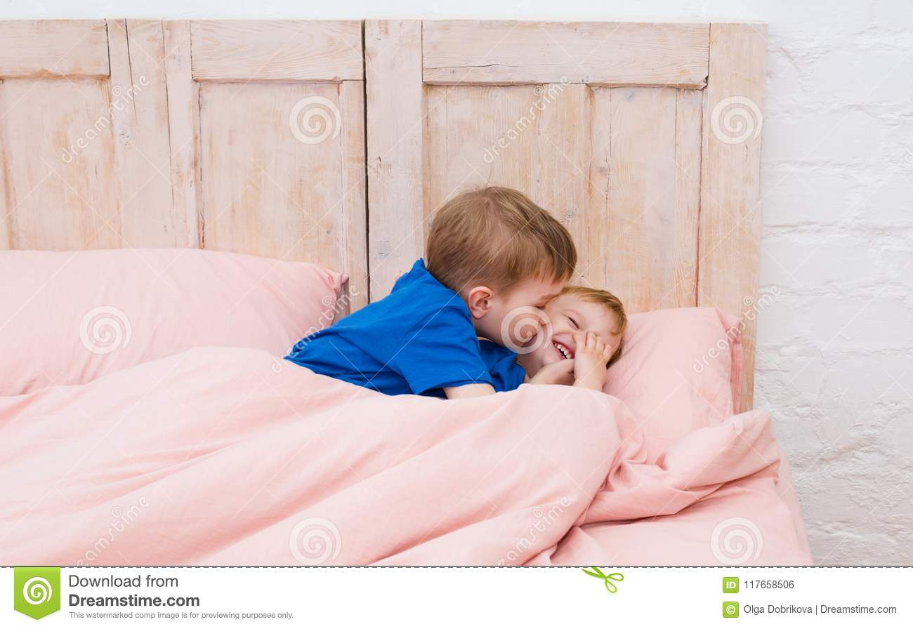 Two boys smiling under a blanket. Brothers kissing and playing.
