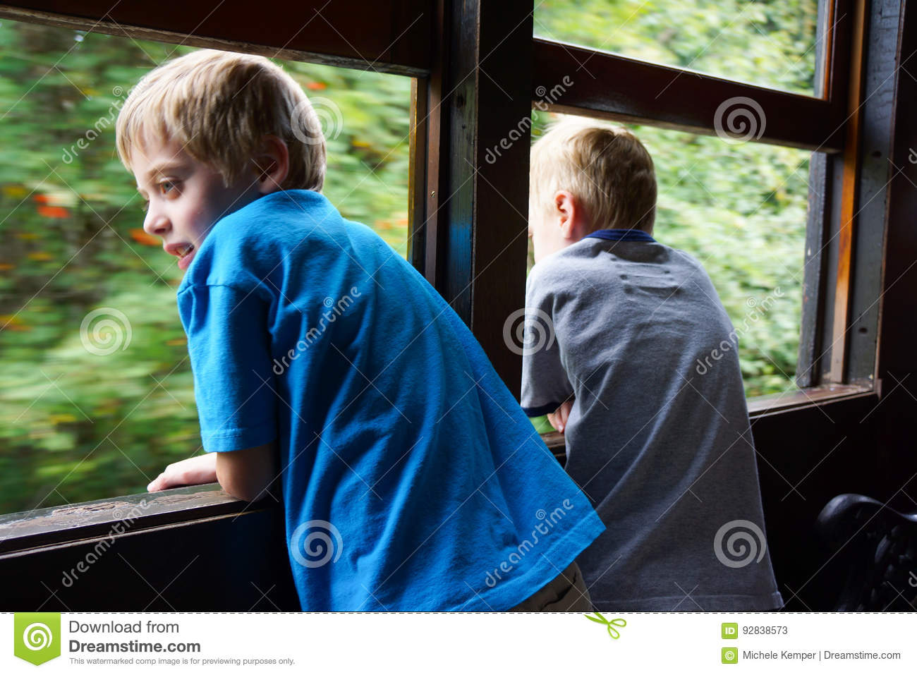 Young boys looking out train window