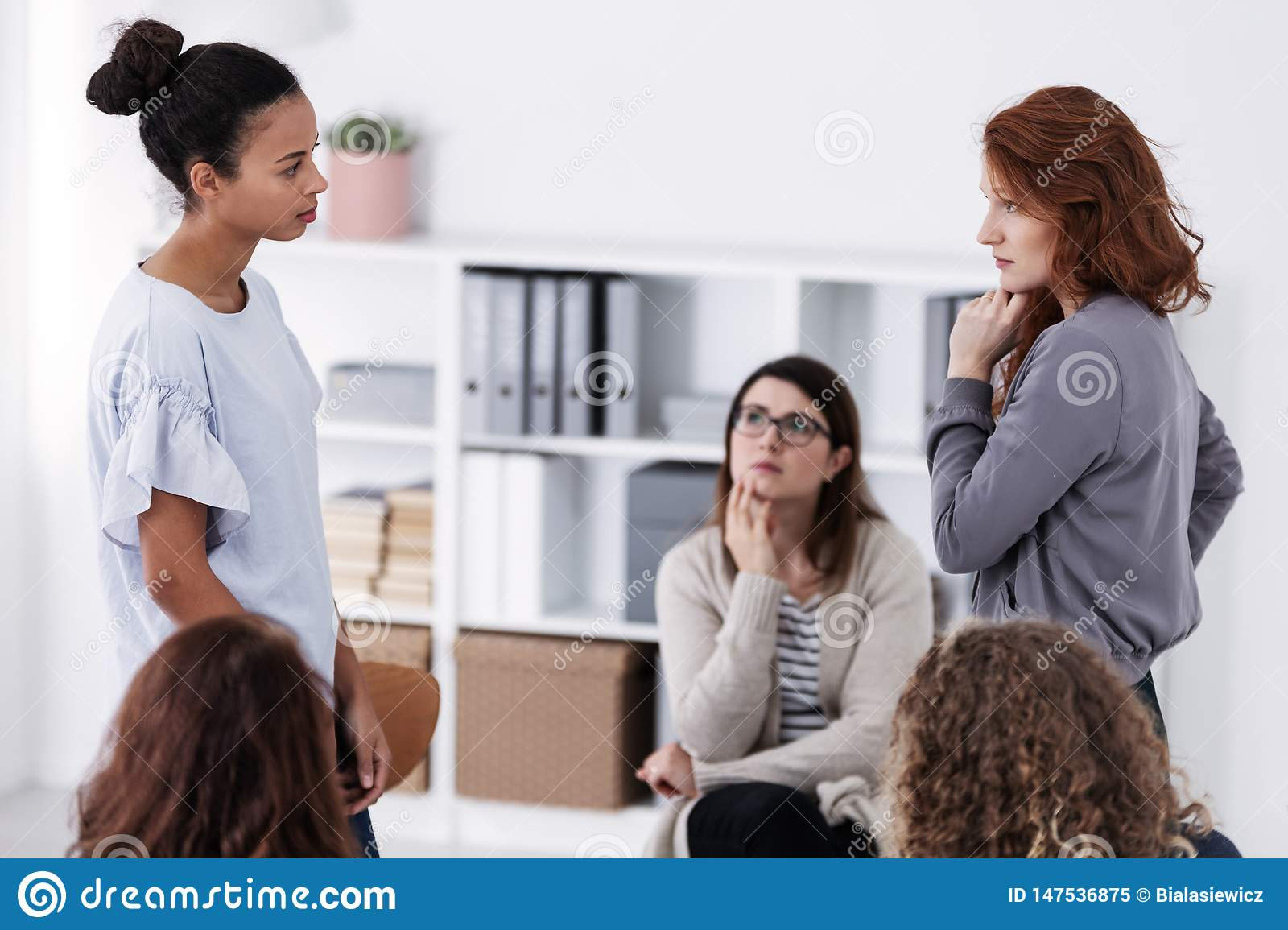 Two brave women standing and looking at each other during role paying at psychotherapy support meeting