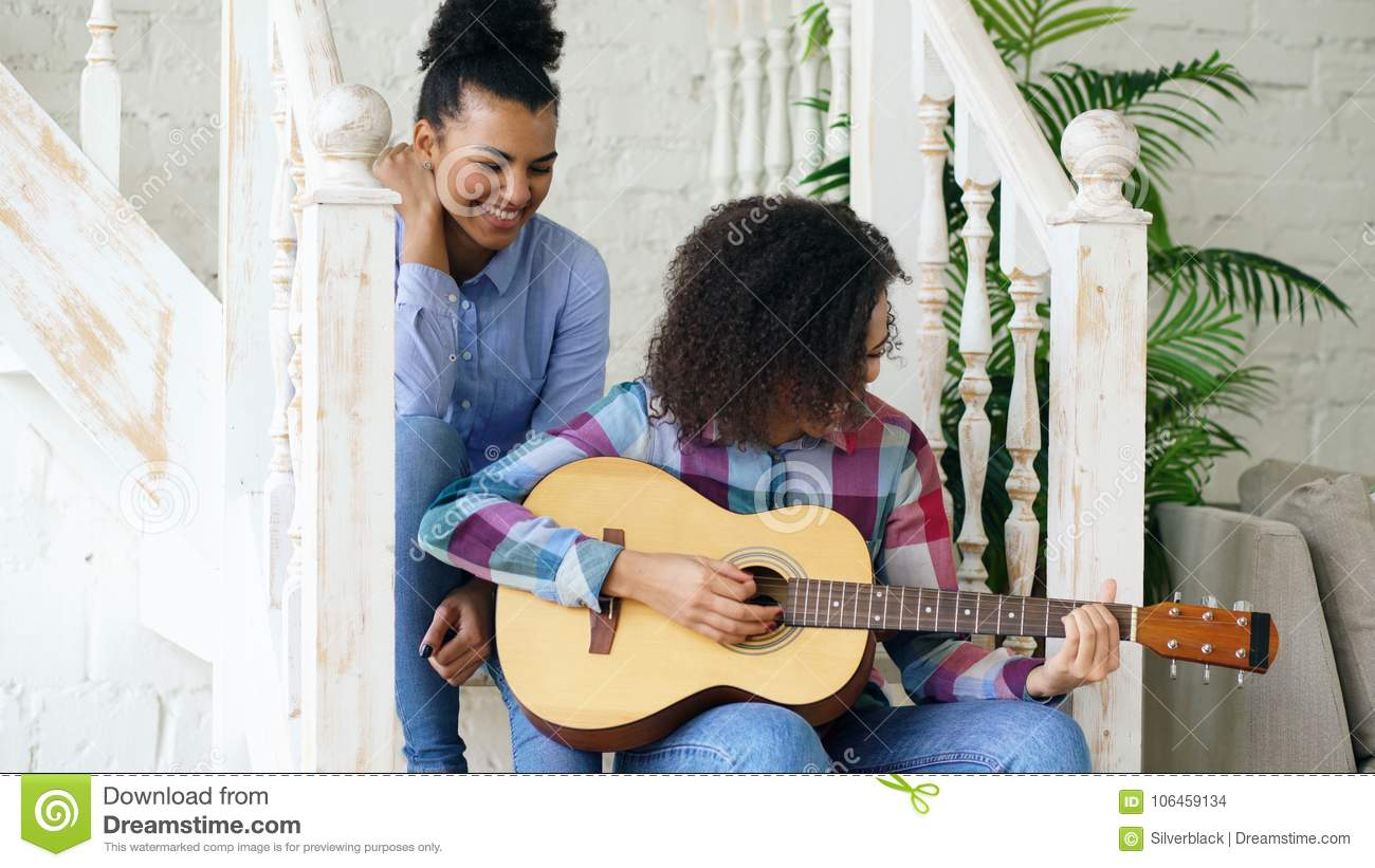 Two brazilian curly girls sistres sitting on stairs and practice to play acoustic guitar. Friends have fun and singing