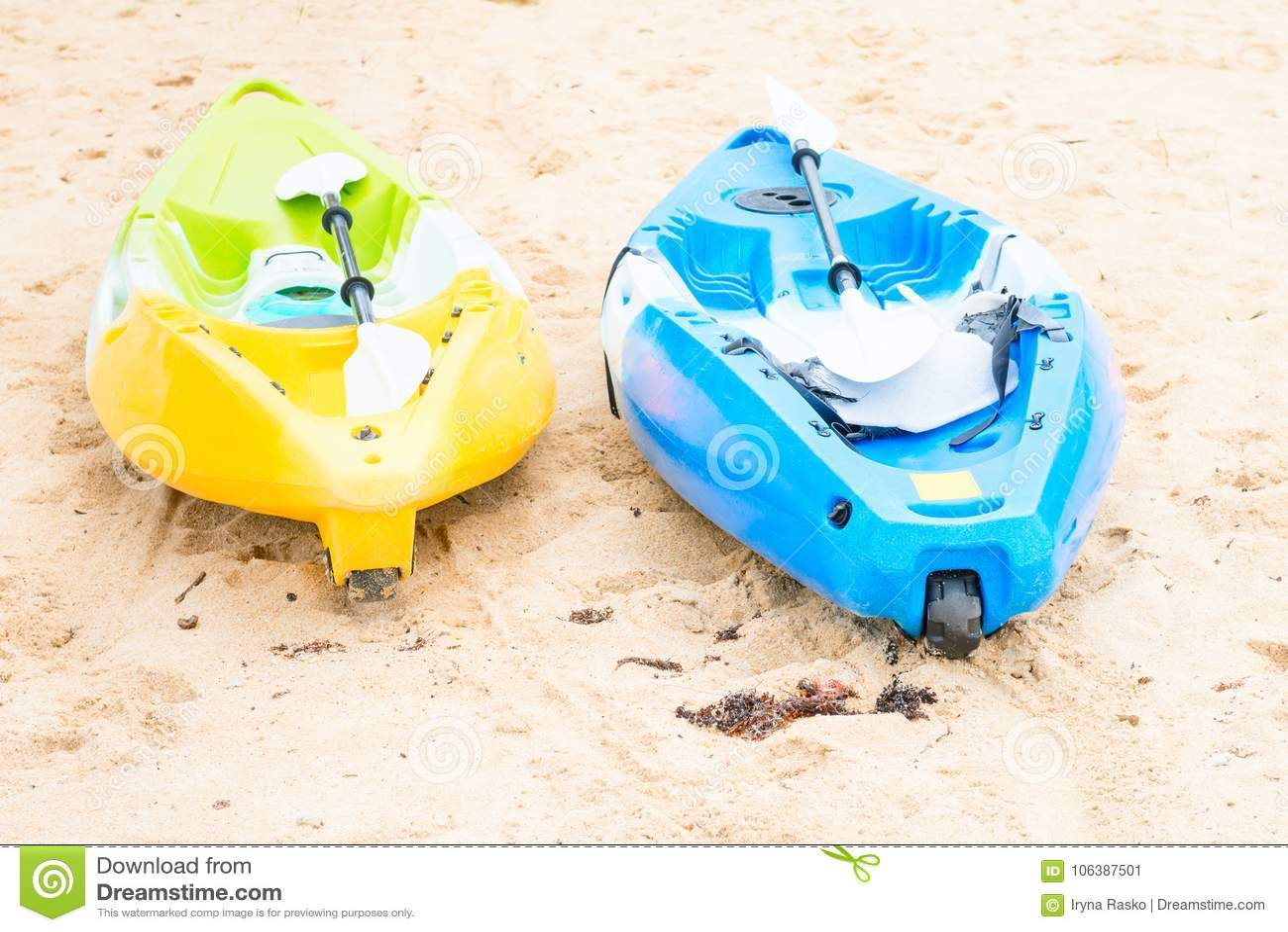 Two bright empty canoe at sand beach