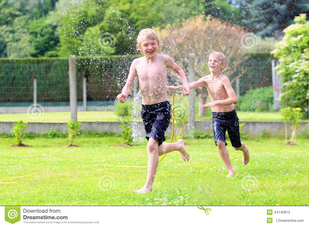 Two brothers playing with water hose in the garden