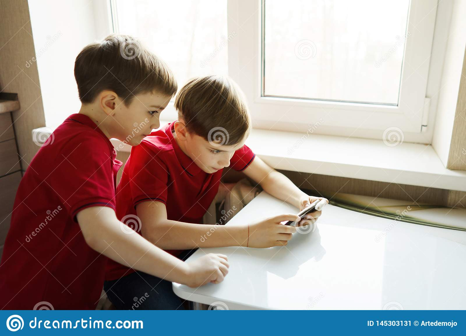 Two brothers are sitting in the kitchen and playing with the phone